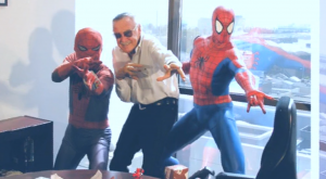 Stan Lee posing with Spider-Man statues